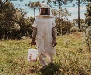 A beekeeper wearing a full heavy cloth beekeeper suit with long cuff gloves.